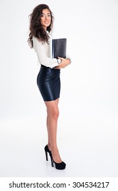 Full length portrait of a smiling young businesswoman standing with folder isolated on a white background. Looking at camera