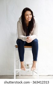 Full length portrait of a smiling young woman sitting on chair