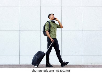 Full length portrait of smiling young man walking with luggage and mobile phone