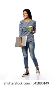Full length portrait of smiling young woman walking with laptop and cup of coffee. Looking at left. Isolated on a white background