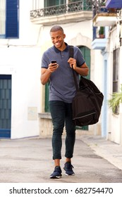 Full length portrait of smiling young black guy traveling with bag and using mobile phone on the street