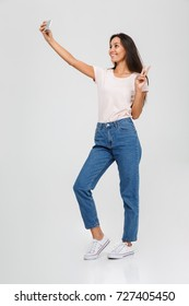 Full length portrait of a smiling young asian woman taking a selfie and showing peace gesture isolated over white background