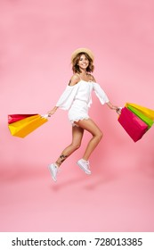 Full length portrait of a smiling young girl holding shopping bags while jumping and looking at camera isolated over pink background