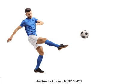 Full length portrait of a soccer player kicking a football isolated on white background