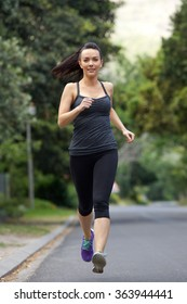 Full length portrait of a sports woman running on street