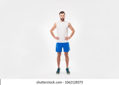 Full length portrait of sporty, sweat, athletic man in t-shirt, holding hands on waist, looking at camera, standing over white background