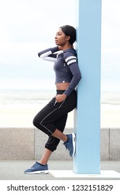 Full length portrait of sporty young black woman leaning against pole outside