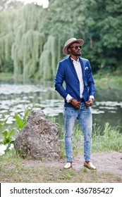 Full length portrait of stylish black man at jacket, hat and sunglasses