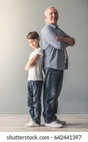Full length portrait of stylish grandpa and grandson in jeans looking at camera while standing back to back with crossed arms