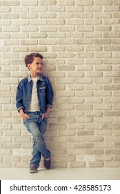 Full length portrait of stylish little boy in jeans clothes looking away and smiling, standing with hands in pockets against white brick wall