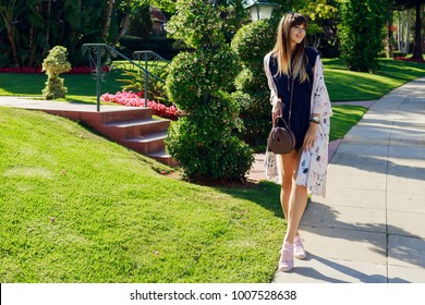 Full length  portrait of stylish smiling woman walking  on  exotic street near the hotel in sunny hot  day . Spending her vacation in Los Angeles.