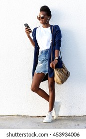 Full length portrait of stylish woman standing against white wall and listening to music on her mobile phone