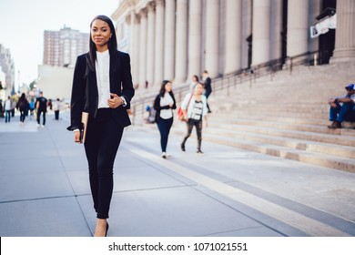 Full length portrait of successful african american student of faculty of law strolling with folder in hand near university.Positive female employee with dark skin in formal wear walking outdoors