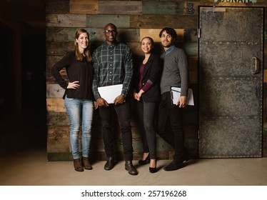 Full length portrait of successful business team standing in an office. Multiracial business professional posing for camera.