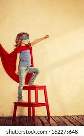 Full length portrait of superhero kid against grunge wall background