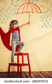 Full length portrait of superhero kid. Strong child against grunge wall background