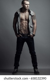 Full length portrait of tattooed brutal young man with short hair, bristle on face wearing sleeveless jacket, blue jeans, sneakers, posing over gray background. Hipster style. Studio shot