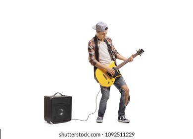 Full length portrait of a teenage boy playing electric guitar connected to an amplifier isolated on white background