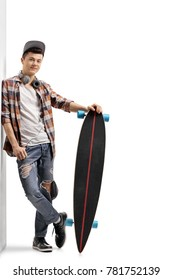 Full length portrait of a teenage hipster with a longboard leaning against a wall isolated on white background