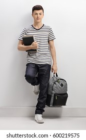 Full length portrait of a teenage student leaning against a gray wall and looking at the camera
