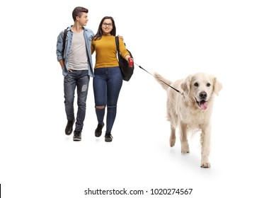 Full length portrait of teenage students walking a dog isolated on white background