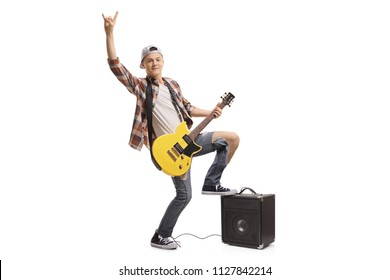 Full length portrait of a teenager with an electric guitar and an amplifier making a rock gesture isolated on white background