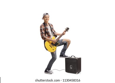 Full length portrait of a teenager playing an electric guitar isolated on white background