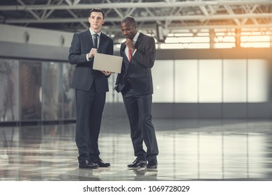 Full length portrait of thoughtful businessmen watching at laptop while locating in warehouse. They leasing premises. Wistful workers watching at laptop concept