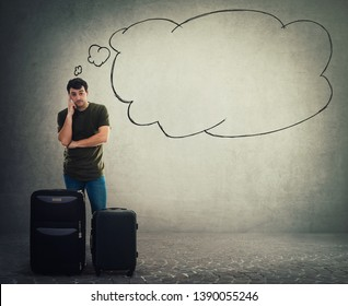 Full length portrait of thoughtful young man traveler standing behind his luggage holding finger to head and waiting. Pensive tourist guy having questions as a thought bubble cloud over head.