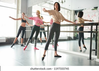 Full length portrait of three elegant young women practicing ballet moves standing by bar against mirror in dance studio, copy space