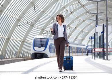 Full length portrait of a traveling business woman walking with bag and phone
