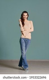 Full length portrait of trendy young woman in beige jersey longsleeve and straight blue jeans