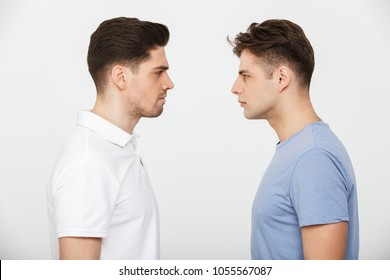 Full length portrait of two angry young men looking at each other isolated over white background