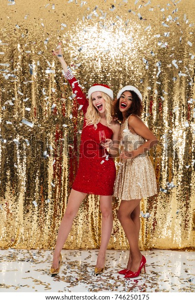 Full length portrait of two cheerful happy girls in christmas hats toasting with champagne glasses while posing and looking at camera isolated over red background
