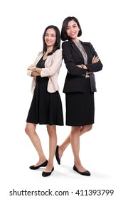 Full length portrait of two confident Asian business women wearing formal dresses, standing over white background