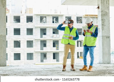 Full length portrait of two contemporary crew workers using VR to visualize projects standing in unfinished building on construction site, copy space
