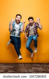 Full length portrait of a two excited young men celebrating while jumping together isolated over yellow background