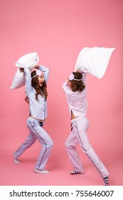 Full length portrait of two excited girls dressed in pajamas having pillow fight isolated over pink background