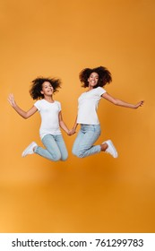 Full length portrait of a two excited afro american sisters jumping and looking at camera isolated over orange background