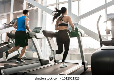 Full length portrait of two fit young people, man and woman, running on treadmills facing windows in modern gym, copy space