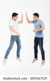 Full length portrait of two happy young men giving high five isolated over white background