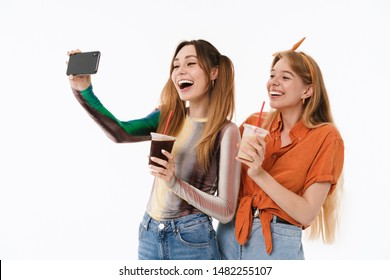 Full length portrait of two positive girls wearing casual clothes taking selfie photo and holding plastic cups isolated over white background
