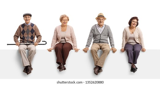 Full length portrait of two senior men and two senior women sitting on a white panel and posing isolated on white background