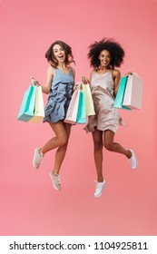 Full length portrait of two smiling young girls dressed in summer clothes holding shopping bags while jumping isolated over pink background