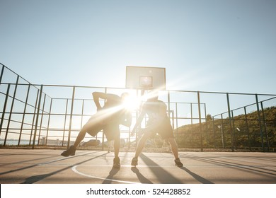 Full length portrait of a two sportsmen playing basketball at the playground