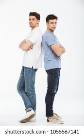 Full length portrait of two upset young men standing back to back with arms folded isolated over white background