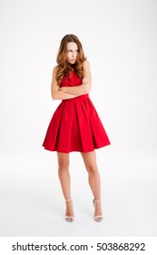 Full length portrait of upset brunette young woman in red dress standing with hands folded and looking away isolated over white background