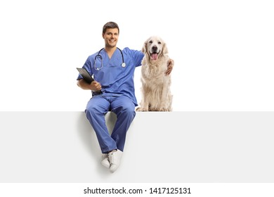 Full length portrait of a veterinarian in a blue uniform sitting on a white panel and hugging a retriever dog isolated on white background