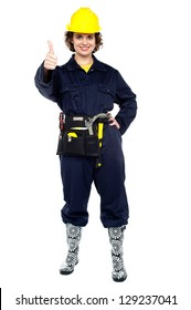 Full length portrait of a woman construction worker showing thumbs up.