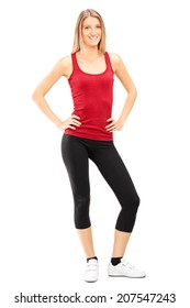 Full length portrait of a woman in sportswear posing isolated on white background